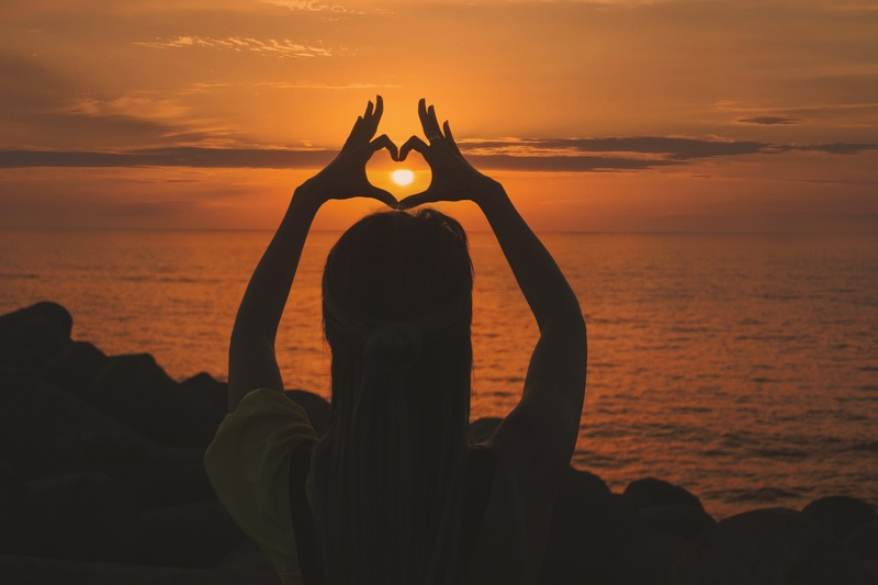 Silhouette of Woman Doing Heart Sign at Sunset