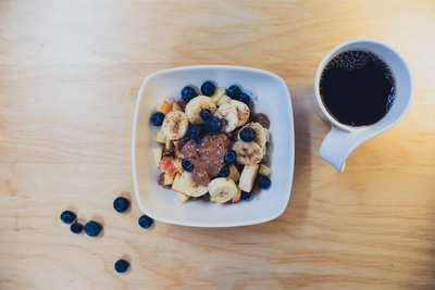 Sliced Bananas with Berries And Peanut Butter Beside Cup of COffee