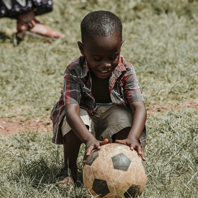Smiling Boy Sitting While Holding Soccer Ball