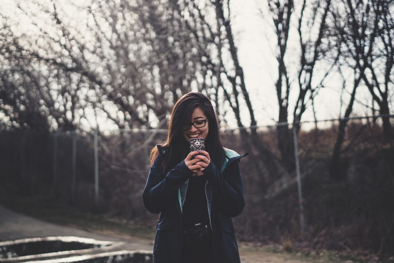 Smiling Woman Holding Smartphone Standing Near Fence with Trees