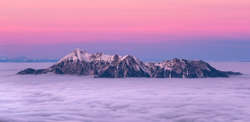 Snow-Capped Mountain Surrounded By Sea of Clouds