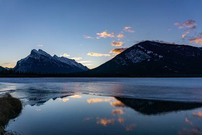 Snowy Mountains Reflect In Water At Sunrise