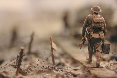 Soldier Walking on Wooden Pathway Surrounded with Barbwire Selective Focus