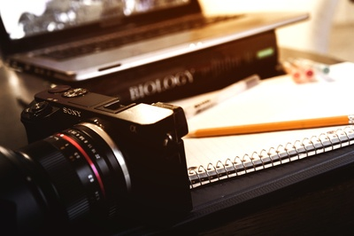 Sony Compact Camera Near Open Spring Notebook And Pencil