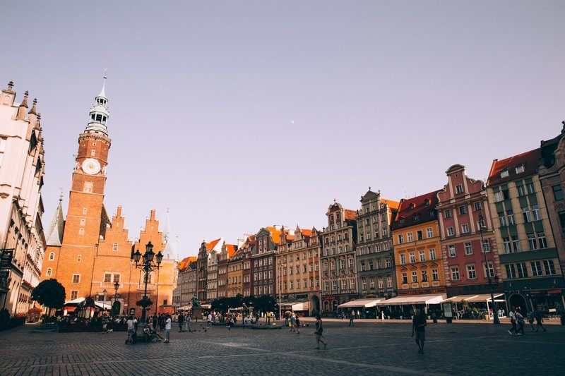 Sunset Over A Red Brick Tower In A Cobbled Piazza