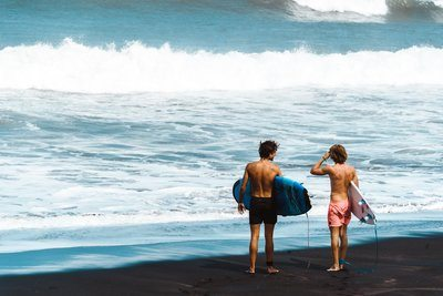 Surfers Stand On Shore