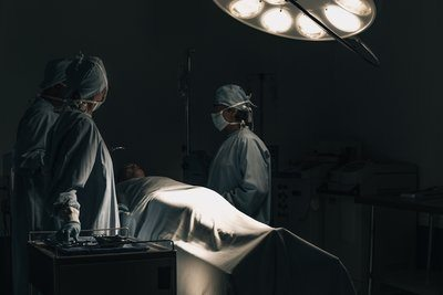 Surgeons Huddled Around A Patient On A Hospital Bed