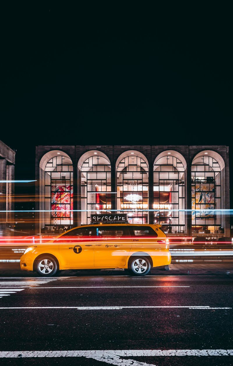 Taxi Races Past Urban Gallery At Night