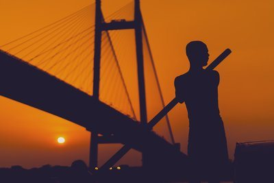 The Silhouette Of A Man Rowing Against A Sunset Orange Sky