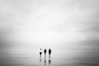 Three Men Walk Out Over A Low-Tide Beach