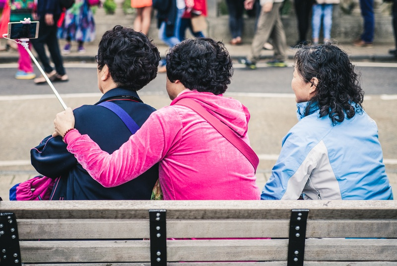 Three Person Taking Selfie While Sitting on A Bench During Day