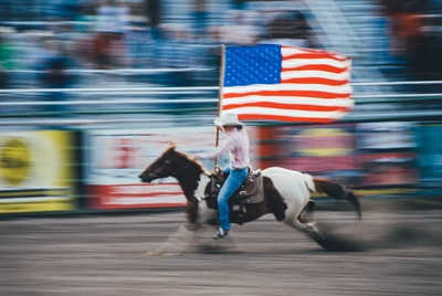 Time Lapse  Man Carrying U.S. Flag While Riding Brown