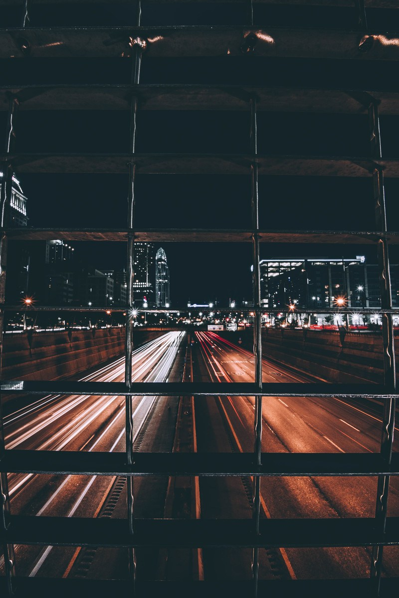 Time-Lapse  Road with Light Streaks View Behind Grills