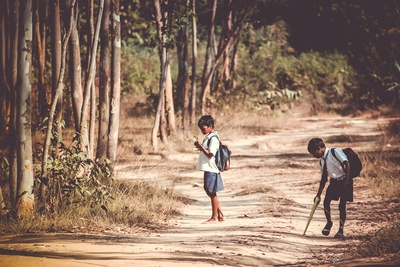 Two Boys Standing on Road Near Tree
