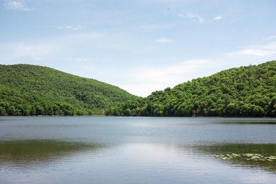 Two Green Hills By A Lake