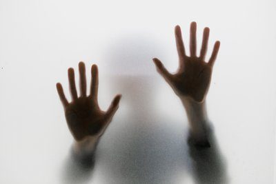 Two Hands Pressed Against Smoked Glass