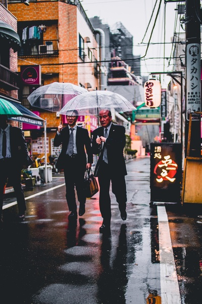 Two Men in Black Suit Holding Transparent Umbrellas Walking in the