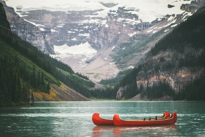 Two Orange Boats in Water in Front of Mountain