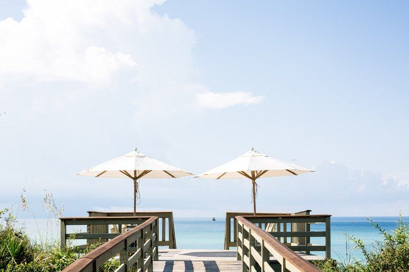 Two Parasols Next To Each Other On A Boardwalk