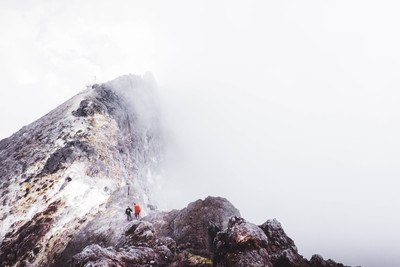 Two People Standing on Mountain Slightly Covered with Fogs