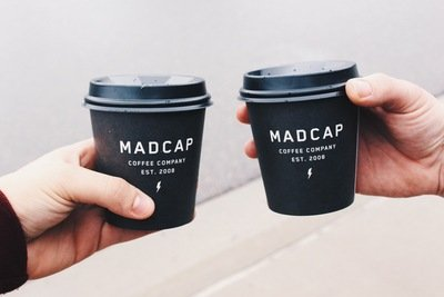 Two Person Holding Black Madcap COffee Disposable Cups