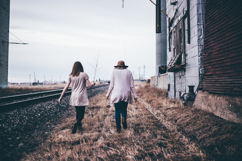 Two Persons Walking Along Railway