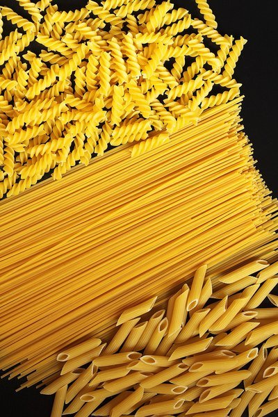 Various Types Of Uncooked Pasta On Black Counter