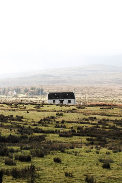 Whit And Black House in the Middle of Wide Open Landscape
