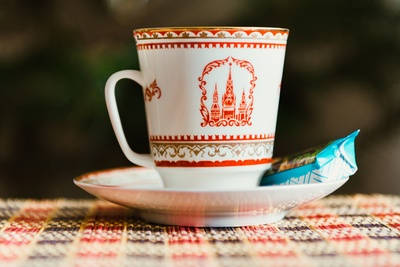 White-And-Red Teacup on Saucer with Blue Labeled