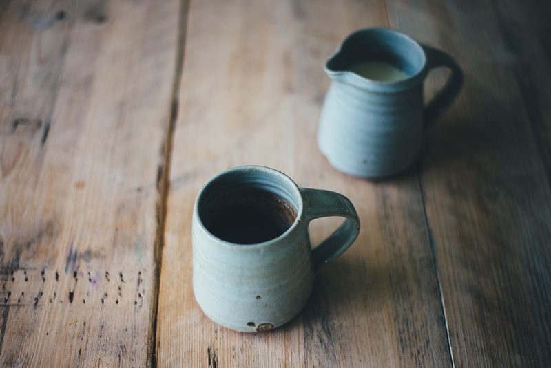 White Ceramic Mug with Brown And White Liquid inside on Brown