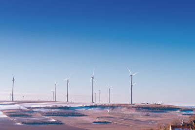 White Wind Turbine on Grey Desert Under Blue And White Sky