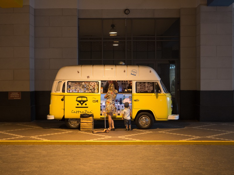 Woman And Child Standing in Front of Yellow Bus in Car