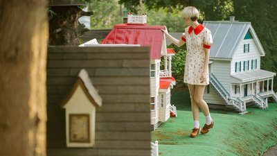 Woman And Dollhouse With Red Roof