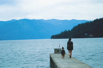 Woman And Girl Walking Along Concrete Dock Surrounded By Body of