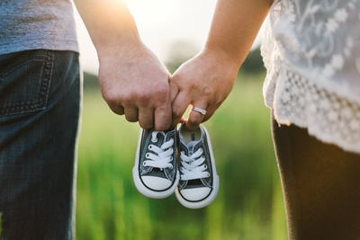 Woman And Man Holding Black Crib Shoes Standing Near Green Grass