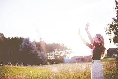 Woman Hands Up in Front of Green Meadows