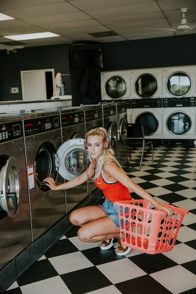 Woman Kneeling in Front of Front-Load Clothes Washer inside Laundry Shop