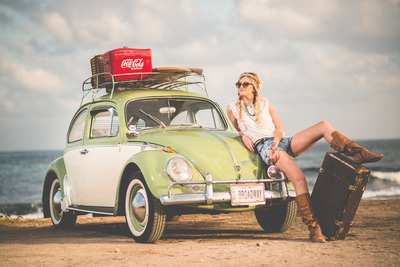 Woman Leaning on Green And White Volkswagen Beetle Near Sea Under