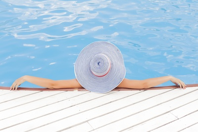 Woman Leaning on White Concrete Surface Beside Swimming Pool