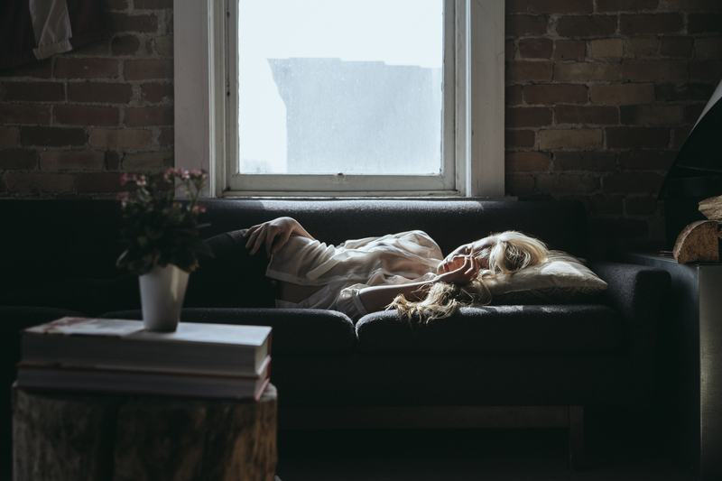 Woman Lying on Sofa Near Closed Window