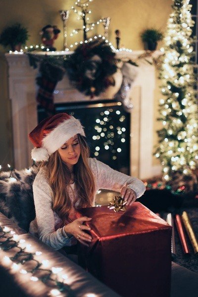 Woman Putting Ribbon in Red Gift Box Near Lighted Christmas Tree