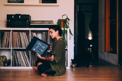 Woman Sits On Floor Looking At Records