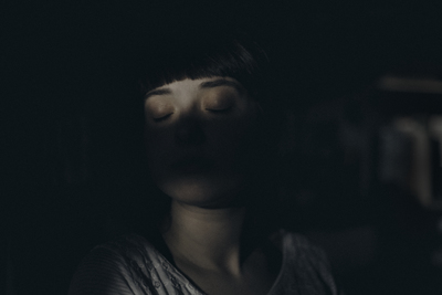Woman Sitting inside Dark Room