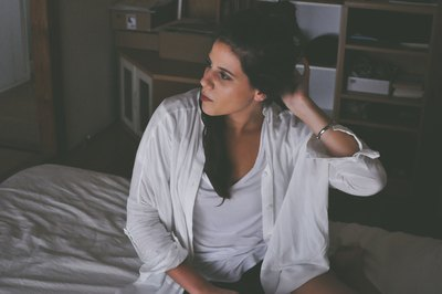 Woman Sitting on Bed Touching Her Hair inside Room