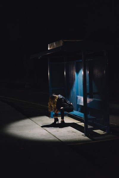 Woman Sitting on Black Weight Bench at Night Time