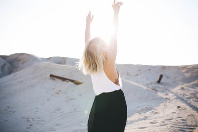 Woman Standing in the Desert with her Hands Up