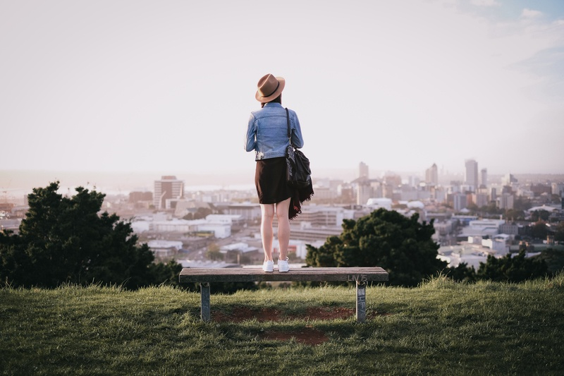 Woman Standing on Bench Facing City Skyline