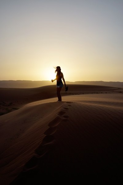 Woman Standing on Sand at Sunset
