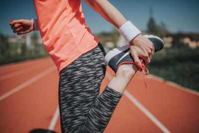Woman Stretching On Track Field