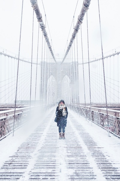 Woman Wearing Black Fur-Lined Coat Standing on the Bridge with Snow